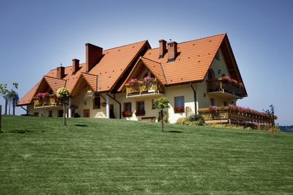 Ein großes Haus mit mehreren Kaminen auf einer Wiese